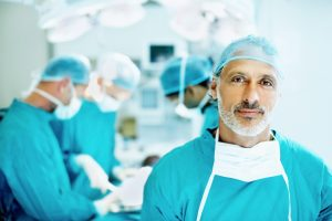 Portrait of senior doctor smiling in the operating theater with team performing surgery in background